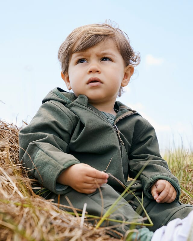 Baby softshell overall made of organic cotton on a meadow.