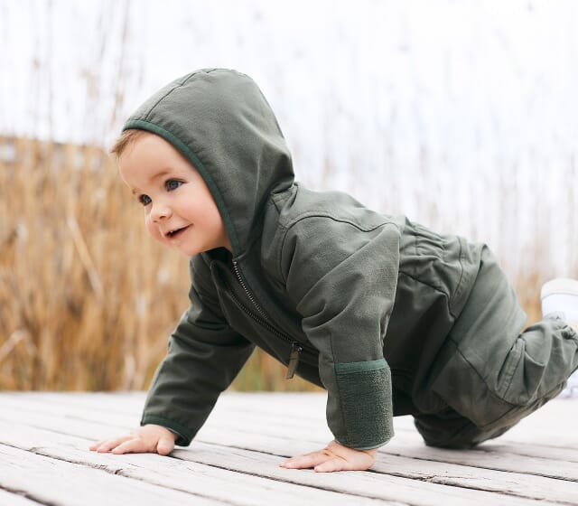 Baby softshell overall made of organic cotton on a bridge.